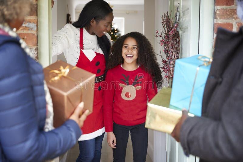 Abuelos que son saludados por la madre y la hija como llegan para la visita el día de la Navidad con los regalos imagenes de archivo