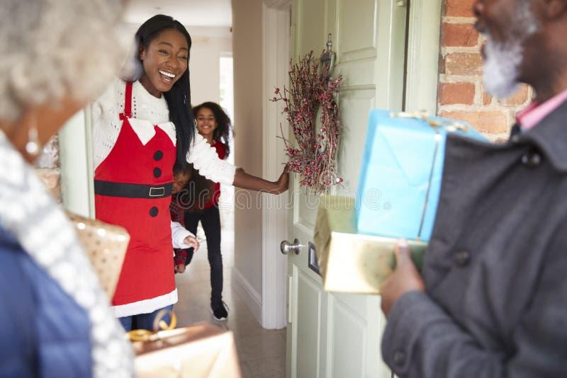 Abuelos que son saludados por la madre y los niños como llegan para la visita el día de la Navidad con los regalos imágenes de archivo libres de regalías
