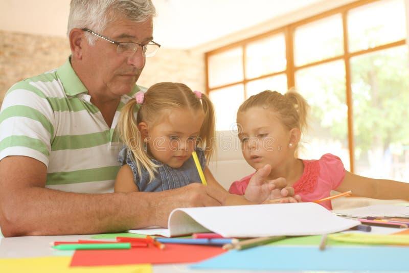 Abuelos que trabajan la preparación con las nietas foto de archivo