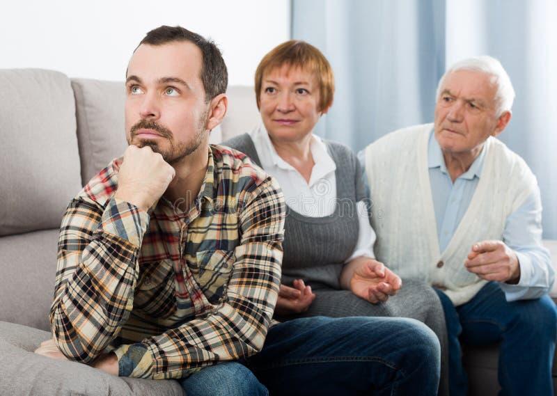 Abuelos y charla seria del nieto fotografía de archivo