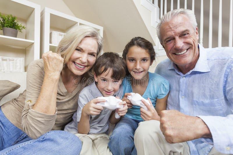 Abuelos y familia de los niños en los juegos video fotografía de archivo