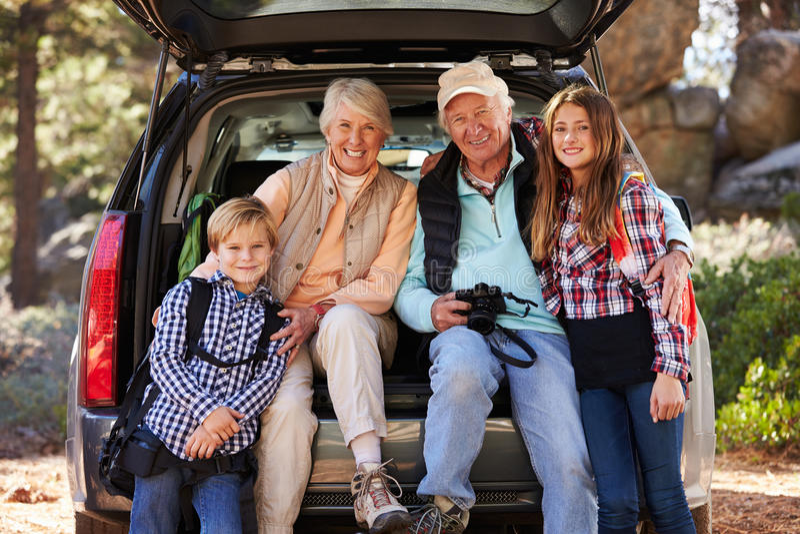 Abuelos y grandkids en la parte posterior del coche antes de caminar fotos de archivo libres de regalías