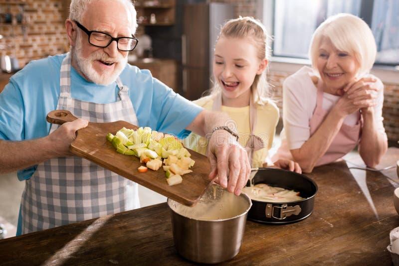 Abuelos y muchacha que cocinan junto imágenes de archivo libres de regalías