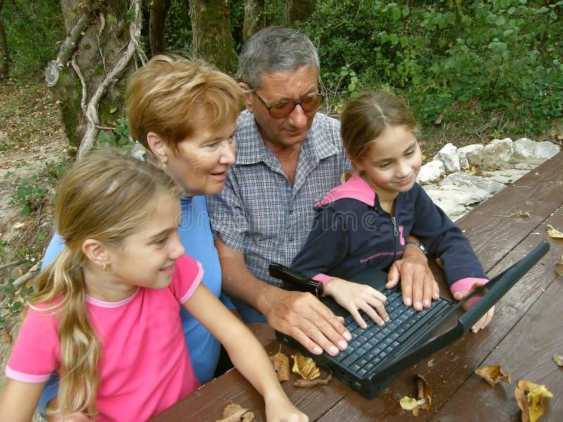 Abuelos y nieta con la computadora portátil imágenes de archivo libres de regalías