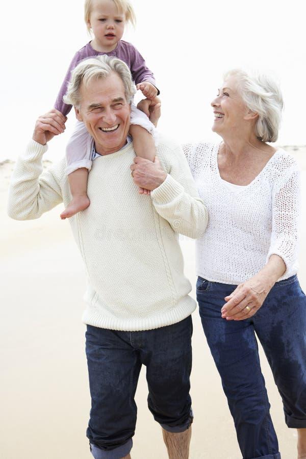 Abuelos y nieta que caminan a lo largo de la playa junto fotos de archivo libres de regalías