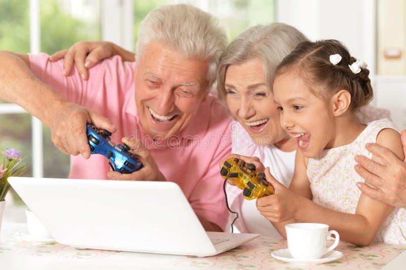 Abuelos y nieta que juegan al juego de ordenador foto de archivo libre de regalías