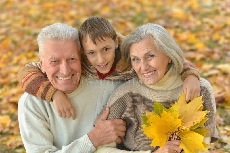 Abuelos y nieto en parque del otoño fotografía de archivo