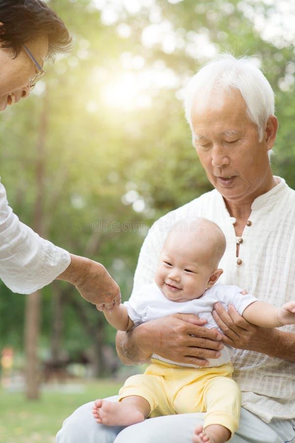 Abuelos y nieto que se divierten al aire libre imagenes de archivo