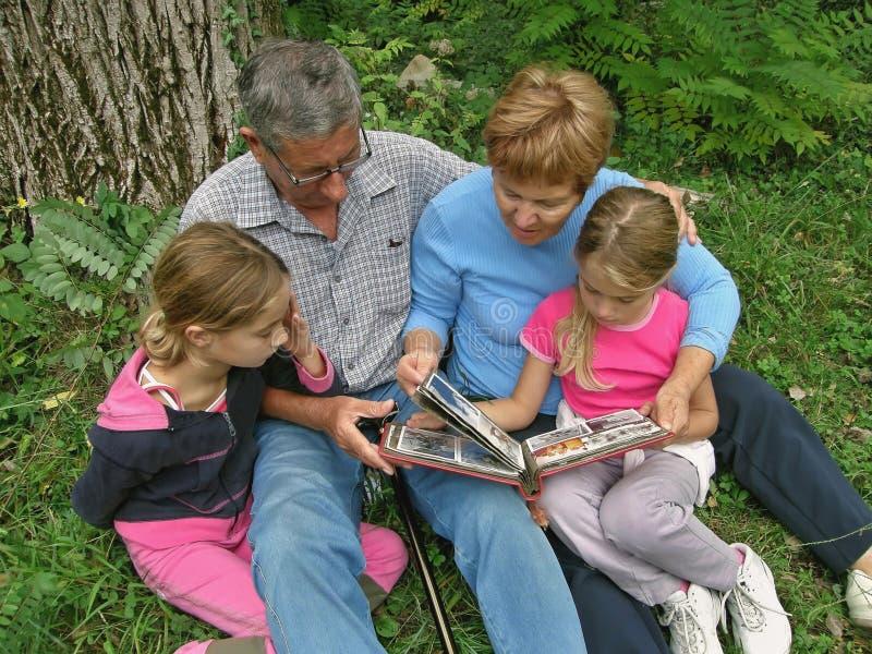 Abuelos y nietos con el álbum de foto imágenes de archivo libres de regalías