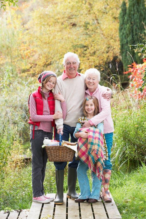 Abuelos y nietos con la cesta de la comida campestre fotos de archivo