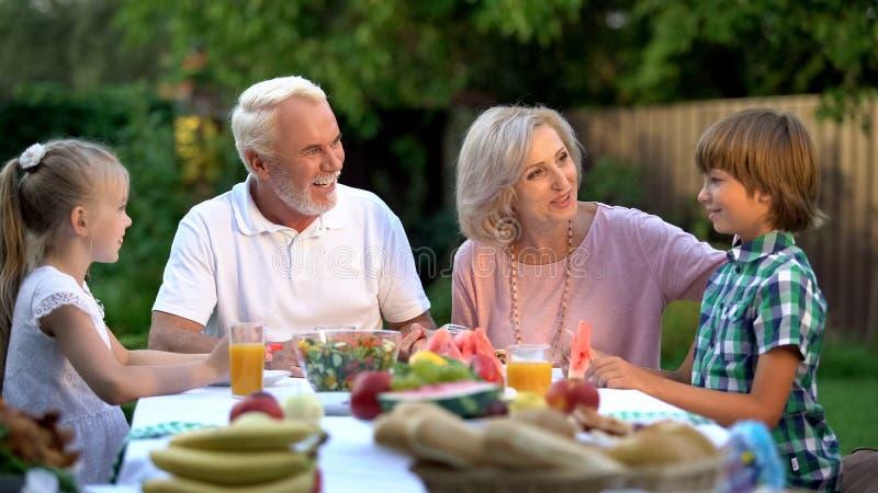 Abuelos y nietos que cenan, pasando fin de semana junto, cabaña imagen de archivo libre de regalías