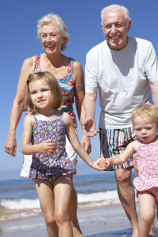 Abuelos y nietos que corren a lo largo de la playa fotos de archivo libres de regalías
