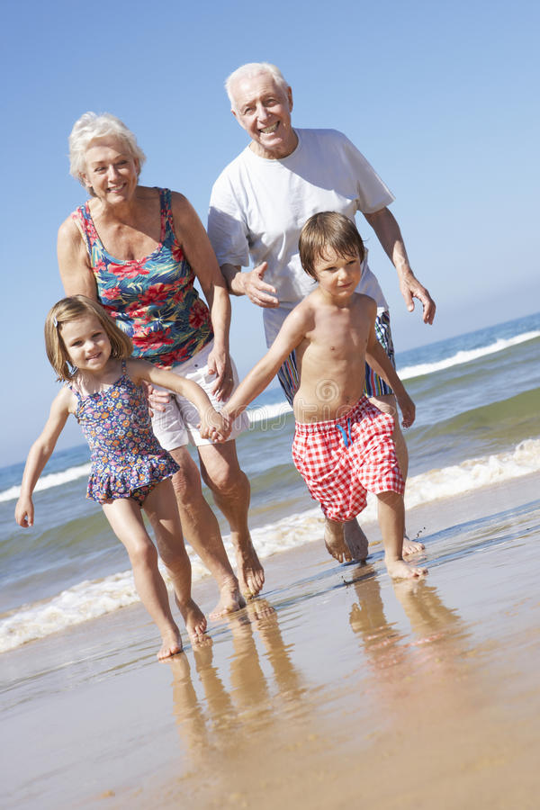 Abuelos y nietos que corren a lo largo de la playa imágenes de archivo libres de regalías
