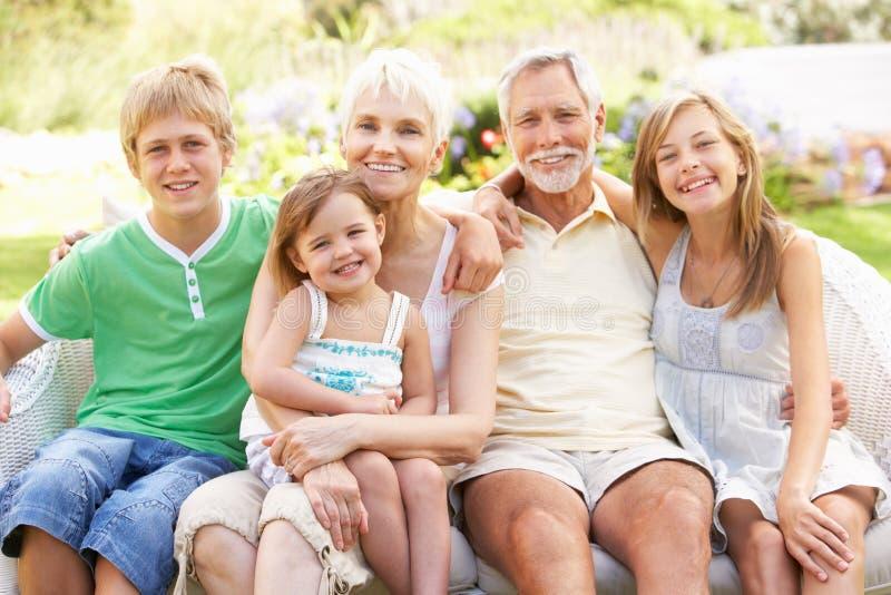 Abuelos y nietos que se relajan en jardín imagen de archivo