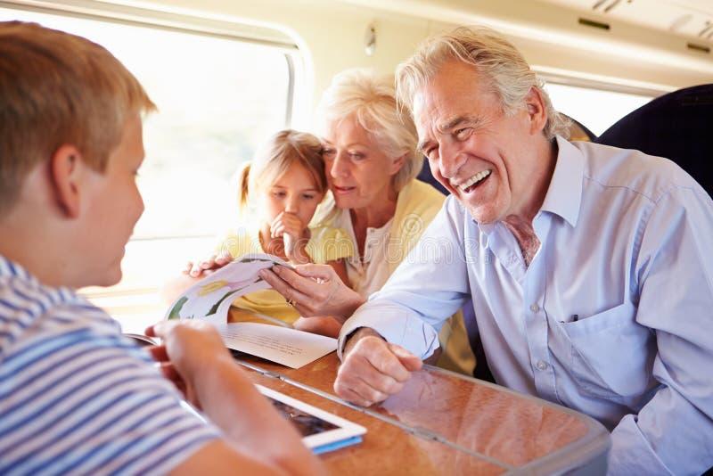 Abuelos y nietos que se relajan en viaje de tren imagenes de archivo