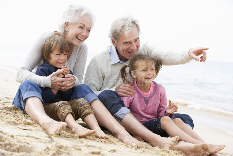 Abuelos y nietos que se sientan en la playa junto imágenes de archivo libres de regalías
