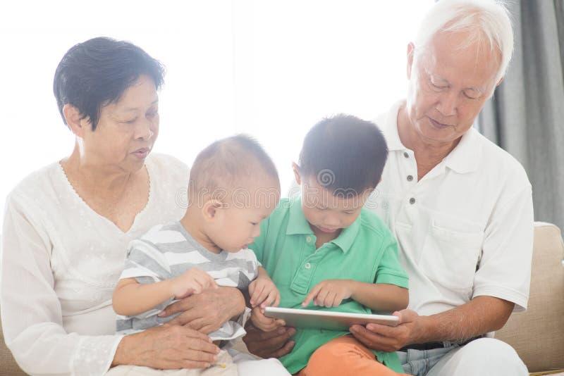 Abuelos y nietos que usan la PC de la tableta fotografía de archivo
