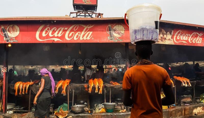 ABUJA, NIGÉRIA, ÁFRICA - 3 DE MARÇO DE 2014: Homem africano não identificado que equilibra a cubeta plástica no mercado de peixes imagem de stock