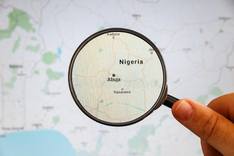 Abuja, Nigeria. Political map. City visualization illustrative concept on display screen through magnifying glass in the hand stock images