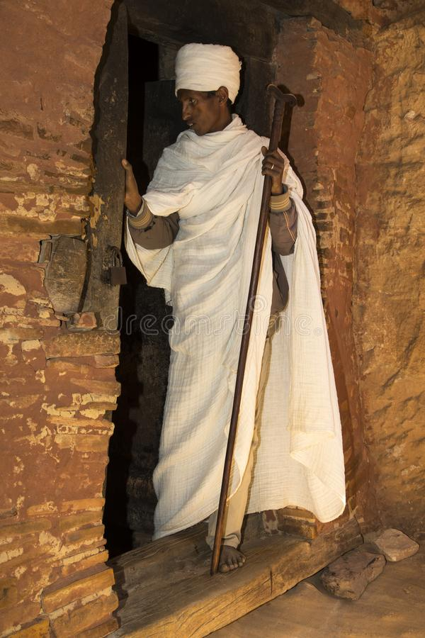 Abuna Yemata Guh, Tigray rock hewn churches. Gheralta massif. Young Ethiopian priest standing at the entrance of the Abuna Yemata Guh rock hewn church in Tigray royalty free stock image