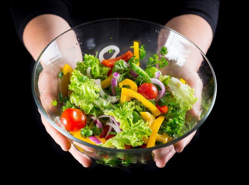 Abundância de vegetais cortados molhados no prato de vidro nas mãos da mulher foto de stock