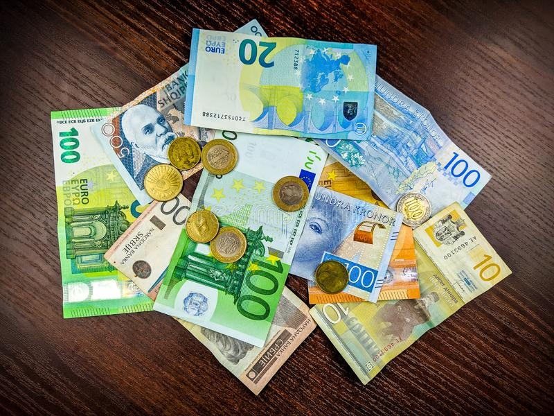 Abundance of financial and international foreign exchange represented in a concept of a pile of different currencies in paper. Money and metal coins stock photo