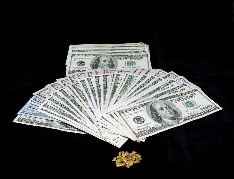 Abundance!. Gold nuggets, 50 and 100 dollar bills on a black background royalty free stock image