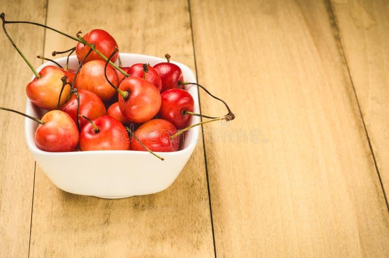 abundancia de cereza dulce en un cuenco blanco en un backgroundabundance de madera de la cereza dulce en un cuenco blanco en un f fotografía de archivo