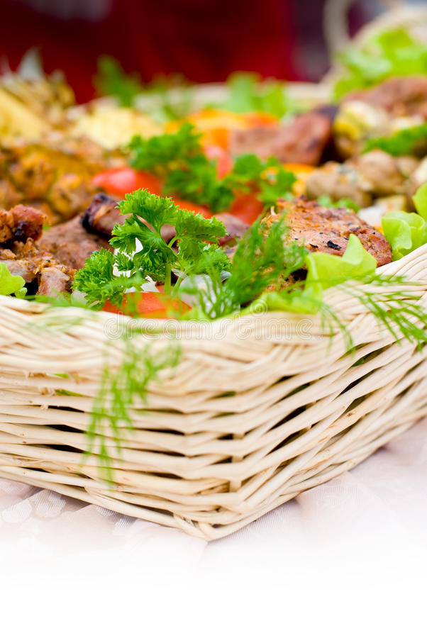 Abundant food basket. Wooden food basket with freshly grilled selection of different types of meat royalty free stock images