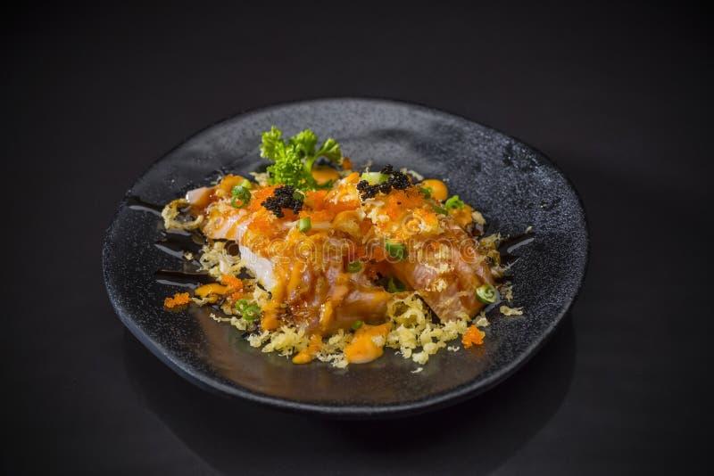 Aburi辣三文鱼Nigiri,被烧的三文鱼寿司和冠上用虾鸡蛋 免版税库存图片