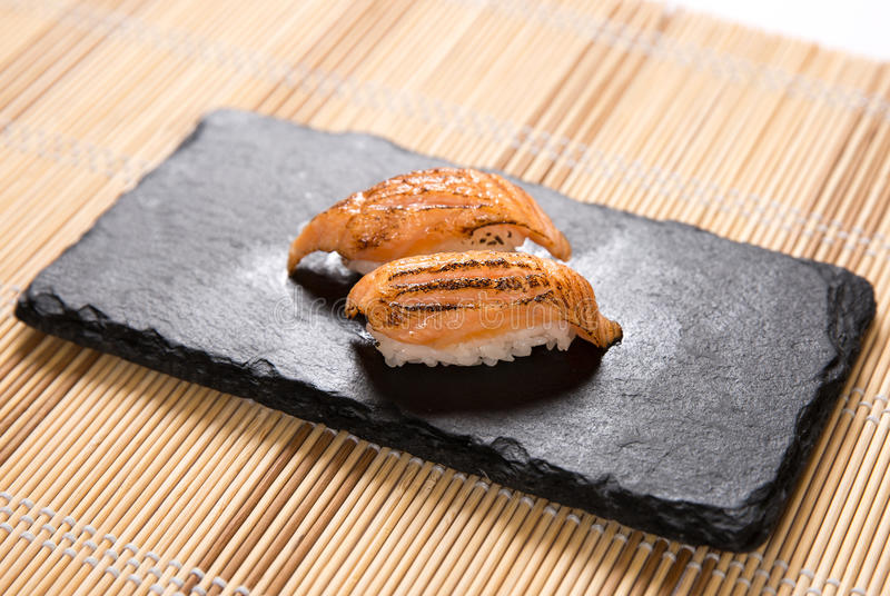 Aburi Salmon Mentai (Torched Salmon Belly) Sushi. Two pieces of torched salmon belly japanese sushi on a stone plate stock images