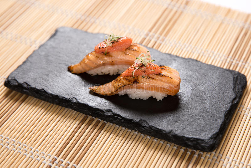 Aburi Salmon (Torched Salmon) Sushi. Two pieces of torched salmon japanese sushi with mentaiko paste on a stone plate stock image