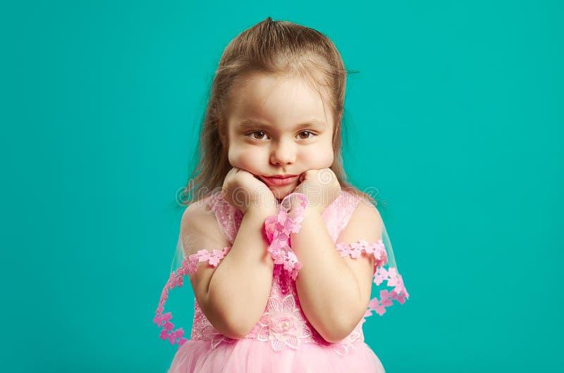 Aburren, tiene a la niña triste una cara frustrada, lleva el vestido rosado hermoso, retrato del niño en mal humor en azul fotografía de archivo libre de regalías