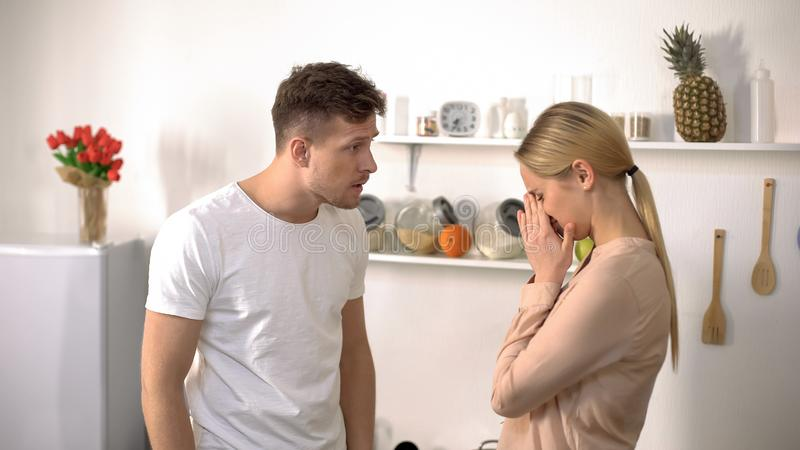 Abuser criticizing wife, woman crying, domestic violence and relationship crisis stock photography