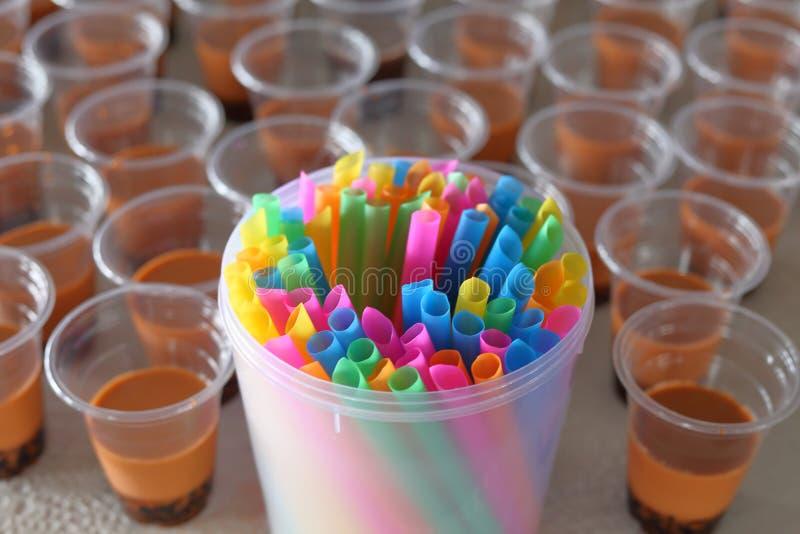 Abuser de la paille et de la tasse en plastique colorées pour le thé de bulle avec le foyer sélectif photos stock