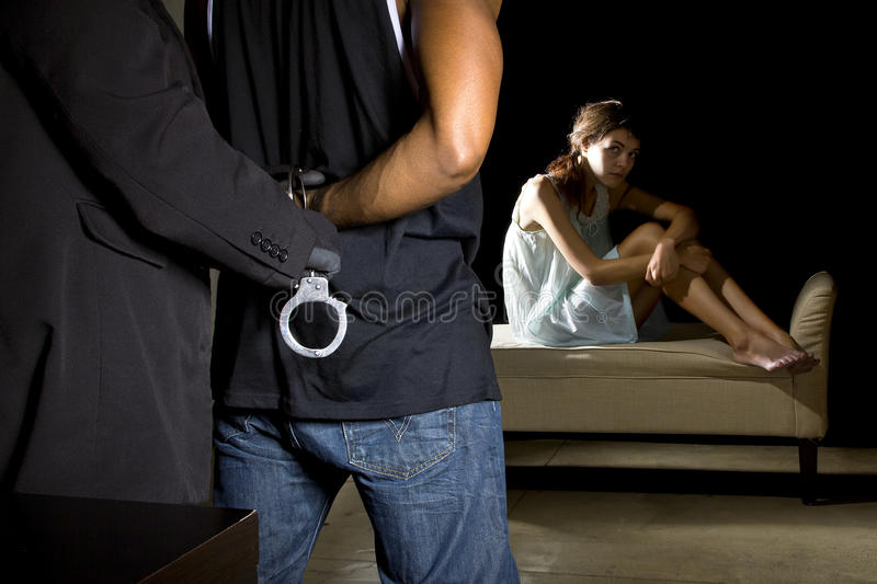Abusive Man Being Arrested for Domestic Violence. Cop arresting a men for domestic violence and female victim in the background stock photos