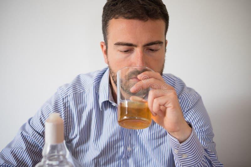 Abuso deprimido do homem do álcool que tenta esquecer seus problemas imagem de stock