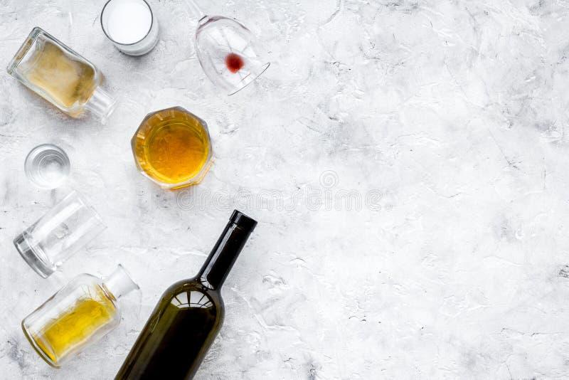 Abuso di alcool Drunkennes Vetri e bottiglie sullo spazio grigio della copia di vista superiore del fondo fotografia stock