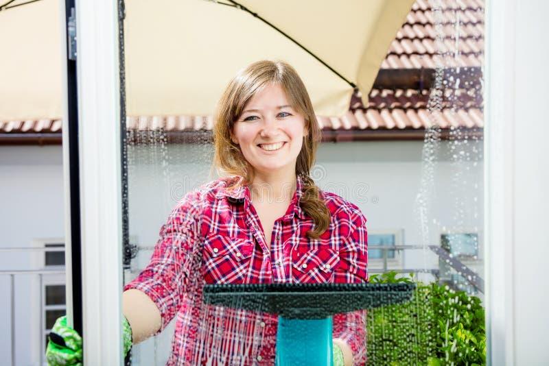Abwaschflüssigkeit und -schwämme Reinigungsfenster der jungen Frau, Abschluss oben stockfotografie