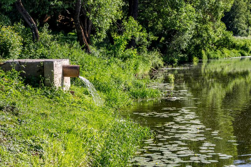 Abwasser vom Rohr in den Fluss stockfotos