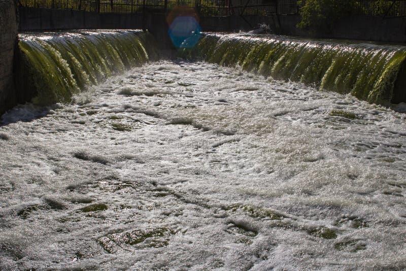 Abwasser von den Kraftwerk-Schadstoffen, die den natürlichen Fluss kommen stockfotos
