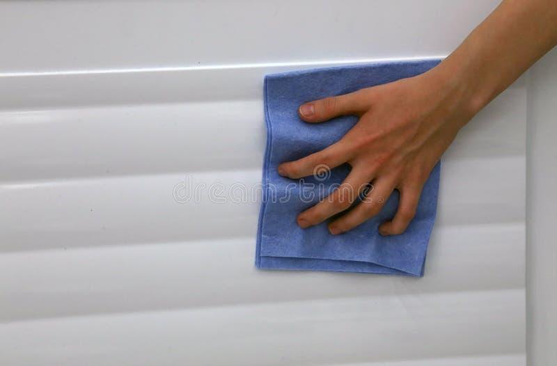 Abwischen der Tür des Kühlschranks mit einem sauberen Stoff stockfotografie