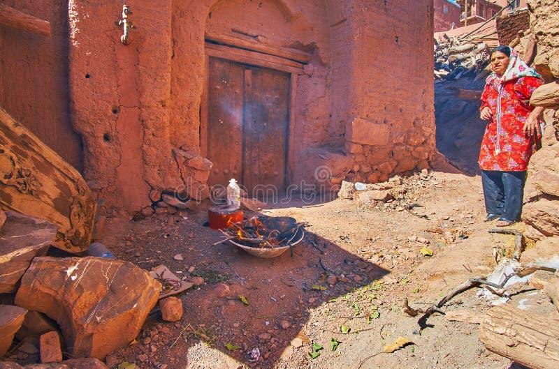 ABYANEH, IRAN - 23 OCTOBRE 2017 : La femme locale dispose à faire cuire la nourriture sur le feu ouvert devant sa maison médiéval photos libres de droits