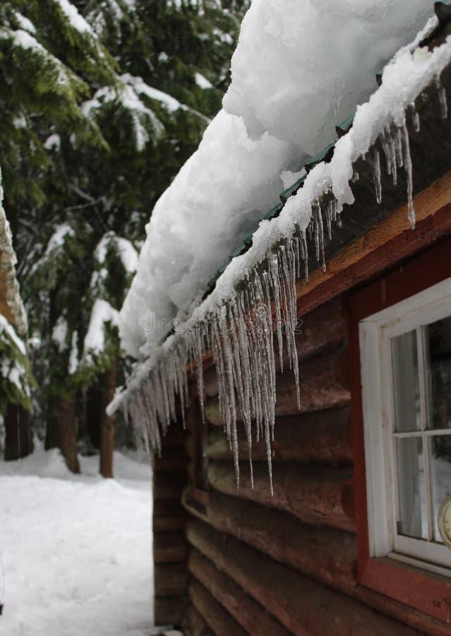 Acúmulo da neve e de gelo no telhado da cabine fotografia de stock