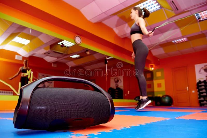 Acústica portátil en el cuarto de los aeróbicos contra la perspectiva de una muchacha borrosa en el entrenamiento cardiio imagen de archivo libre de regalías