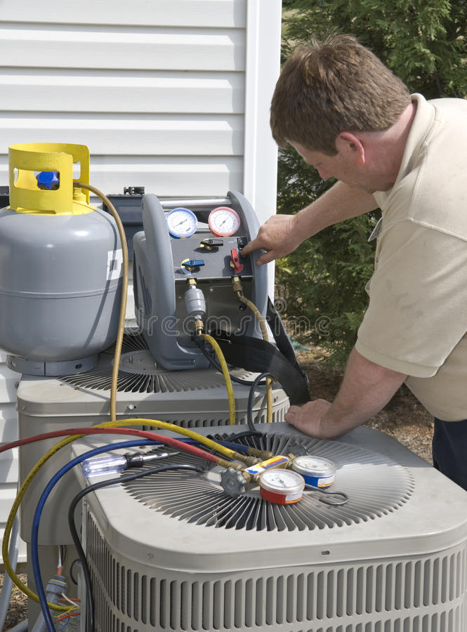 Ac-Repairman Charges Unit With Freon arkivfoton