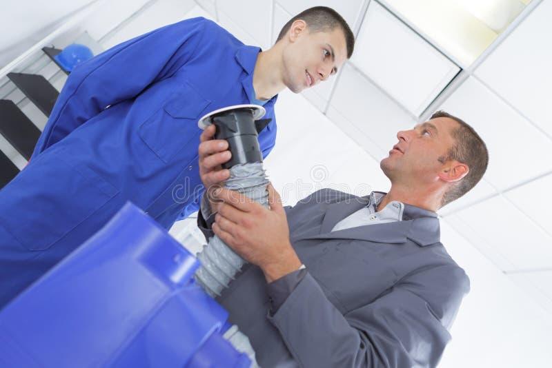 Ac technika nauczyciel pokazuje uczniowi dlaczego instalować mnie zdjęcie stock