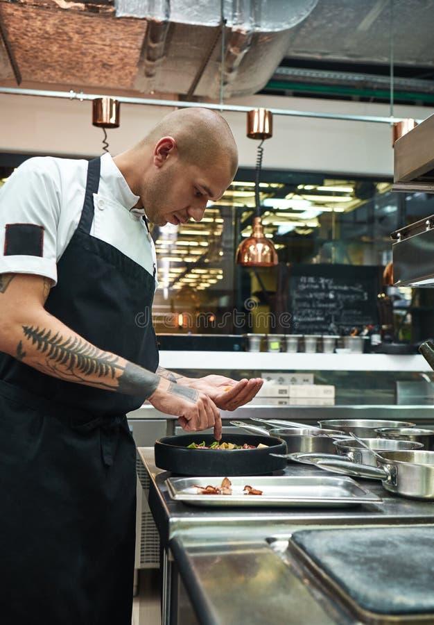 Acabado de un plato Vista lateral del cocinero de sexo masculino joven con varios tatuajes en sus brazos que adorna las pastas it fotografía de archivo libre de regalías