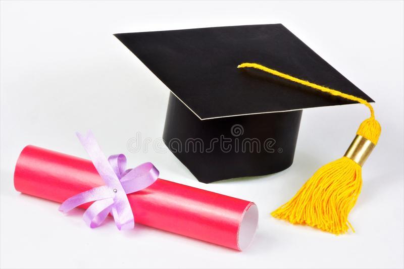 Academic graduation cap student and a scroll diploma. Red document of the graduate student, certificate of graduation from the. University, College and the royalty free stock images