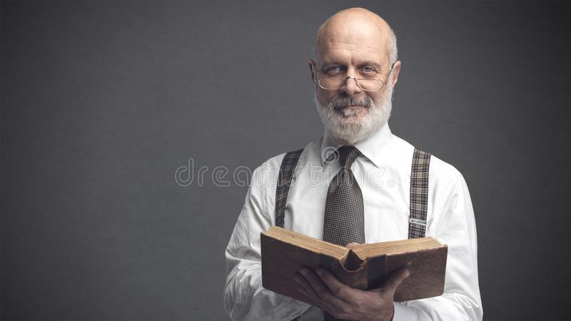 Academic professor smiling and reading a book royalty free stock image